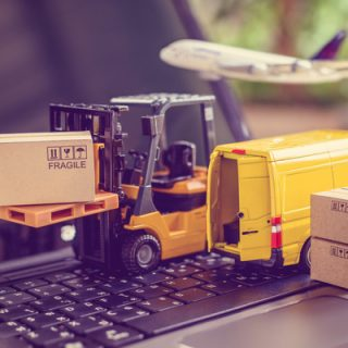 Miniature forklift truck with boxes and Yellow van on laptop