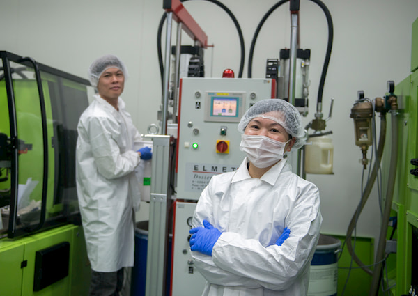 Man and woman wearing a laboratory coat and hairnet inside a laboratory
