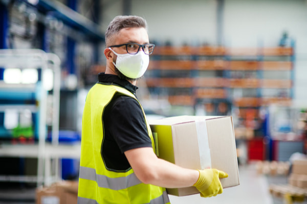 Man worker with protective mask working in industrial factory